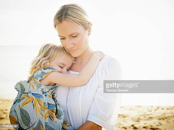 Mother holding daughter on beach at sunset