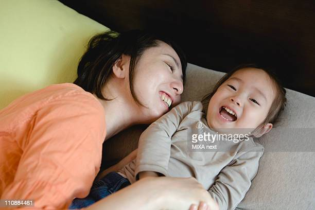 Mother Holding Daughter on Bed