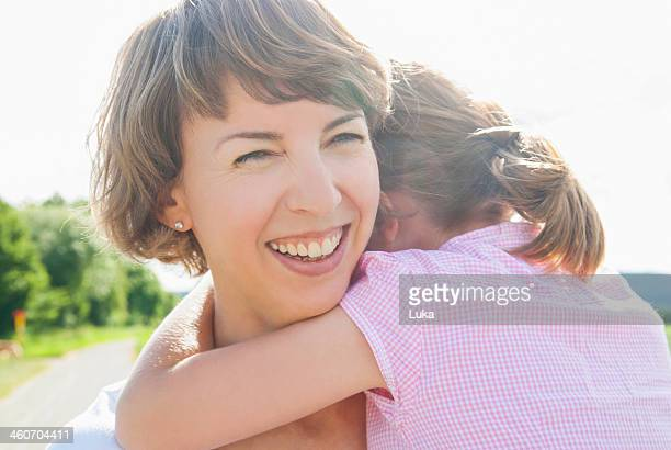 Mother holding daughter, smiling