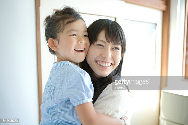 Mother holding daughter, smiling, portrait