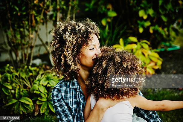 Mother holding daughter while sitting in yard