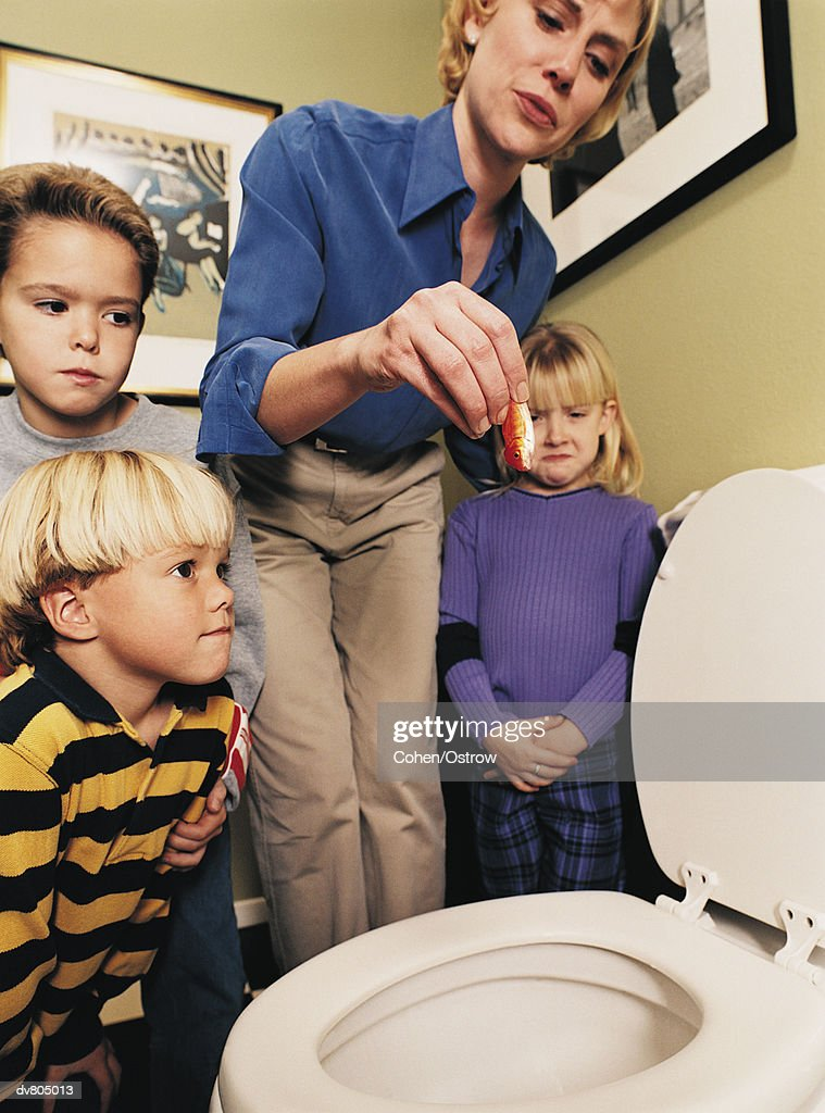 Mother Holding Dead Goldfish over Toilet as Children Watch : Stock Photo