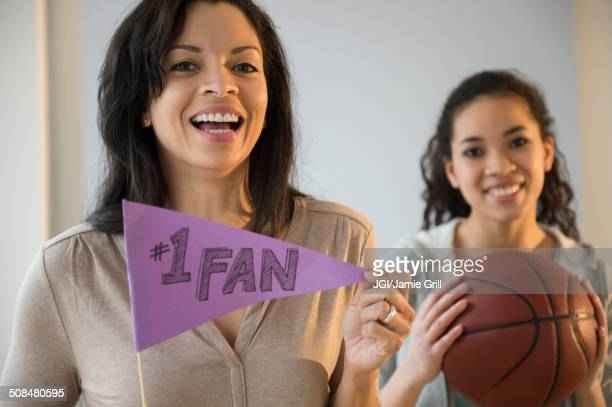 Mother holding fan flag for athlete daughter
