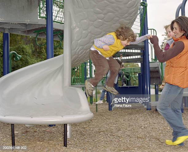 Mother holding girl (2-4), helping boy (4-6) jump from slide