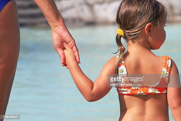 mother holding girls hand at pool