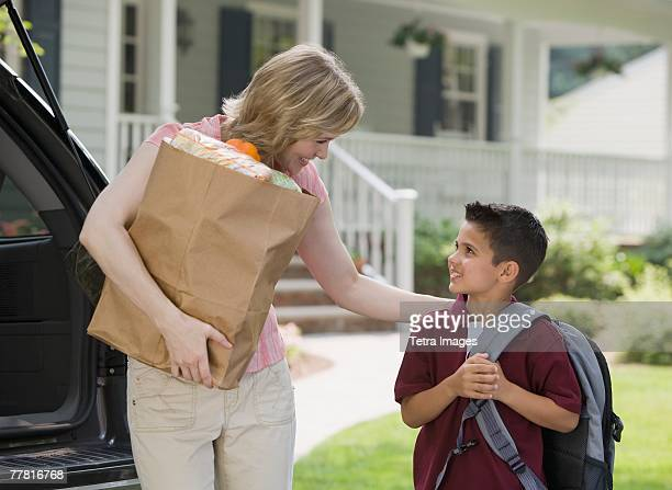 Mother holding groceries and smiling at son