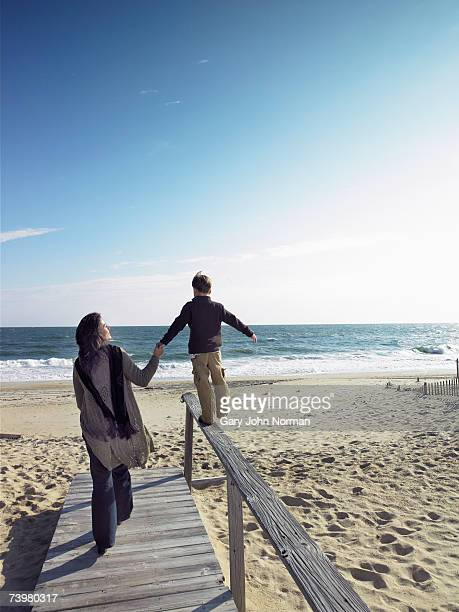 Mother holding hand of son (6-8) walking on railing, rear view