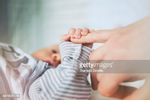 Mother holding her baby hand