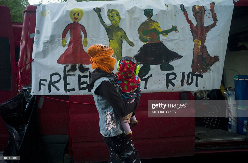 A mother holding her baby walks past a car with a banner reading 'free Pussy Riot' during a demonstration supporting the Russian band Pussy Riot on September 28, 2013 in Prague, Czech Republic. Pussy Riot members were convicted and sentenced to two years in a penal colony in 2012 after they had staged a protest inside a Moscow cathedral.
