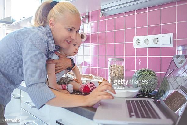 Mère tenant son bébé tout en travaillant sur ordinateur portable à la maison
