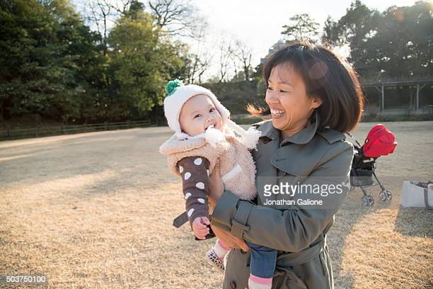 Mother holding her daughter and smiling