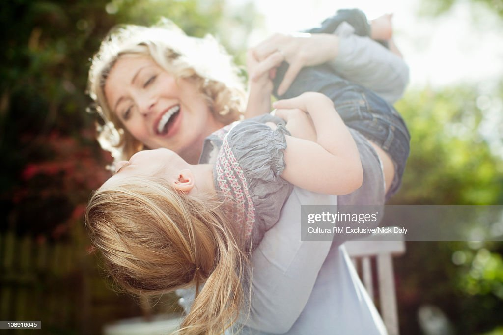 A mother holding her daughter in the air : Stock Photo