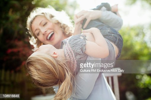 A mother holding her daughter in the air