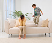 Mother holding her head as son jumps up and down on sofa