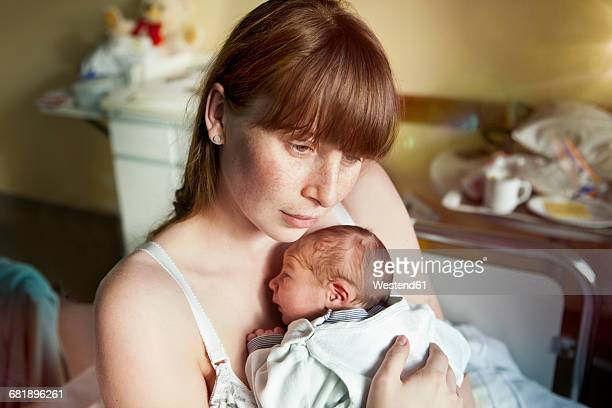 Mother holding her newborn baby in hospital room