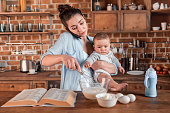 Young mother holding her son, talking on smartphone and mixing a dough at the kitchen. family life and multitasking concept