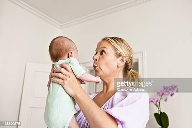 Mutter holding Baby im Schlafzimmer