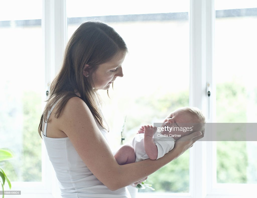 Mother holding infant son by window : Stock Photo