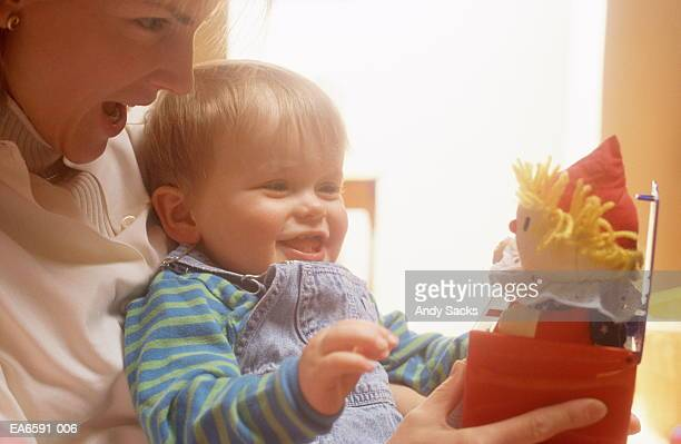 Mother holding male toddler playing with jack-in-the-box