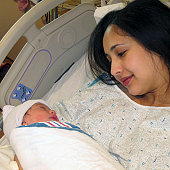 Mother holding newborn baby daughter in hospital