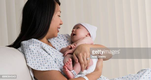 Mother holding newborn daughter in hospital