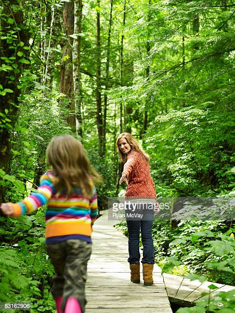 Mother holding out hand to daughter.