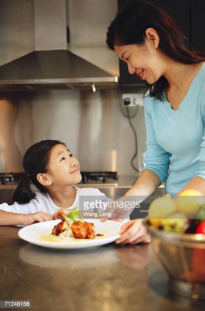 Mother holding plate and looking down at daughter