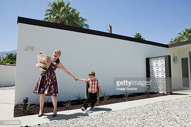 Mother holding shopping bag and pulling son's arm