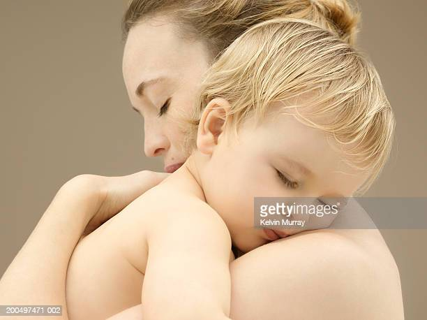 Mother holding sleeping baby boy (9-12 months), close-up