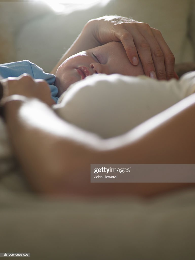 Mother holding sleeping baby son (9-12 months) close-up : Stock Photo