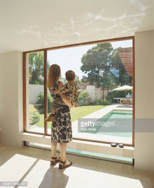 Mother holding son (2-4), looking out window, rear view