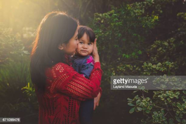 Mother Holding Toddler Daughter In The Woods