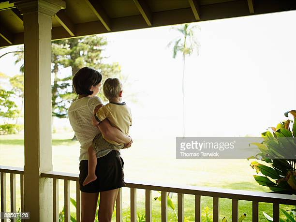Mother holding toddler on porch looking out