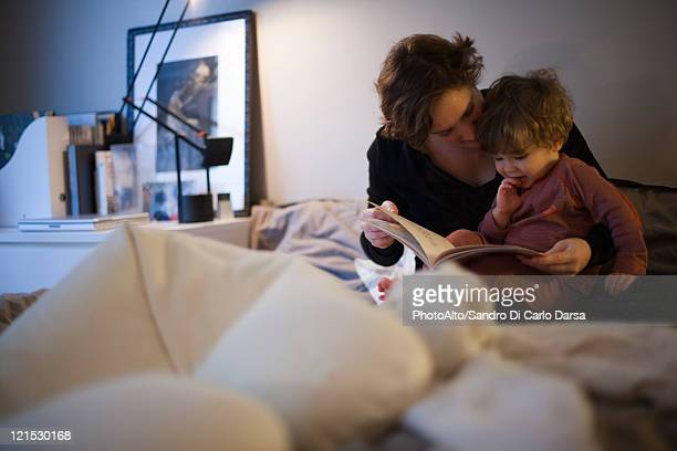 Mother holding toddler son on lap, reading bedtime story in bed