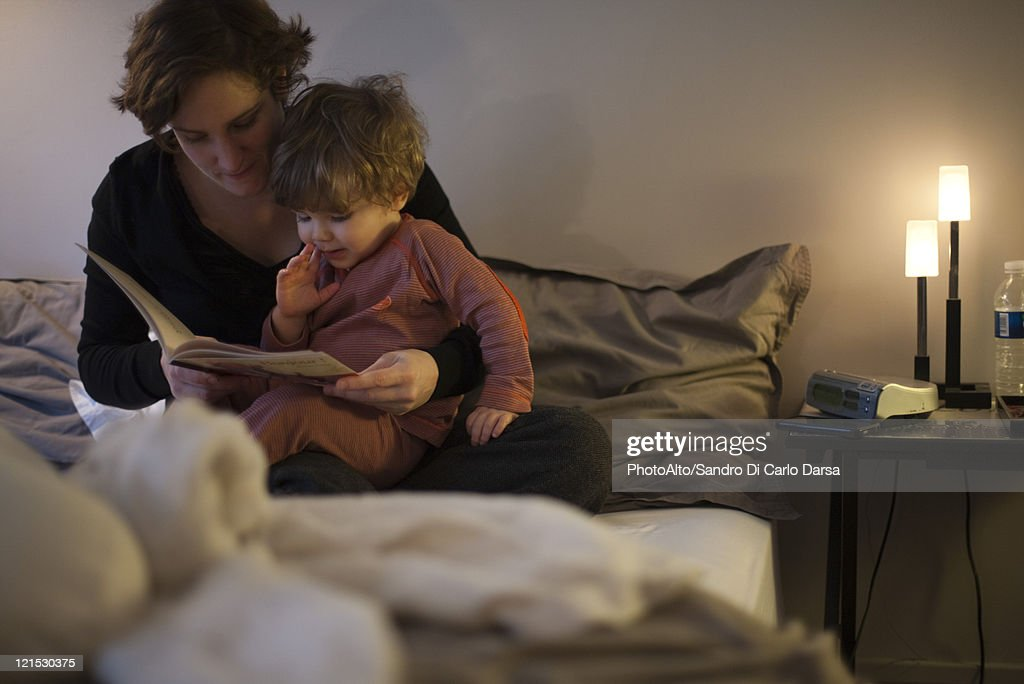 Mother holding toddler son on lap reading bedtime story in for Bed stories online