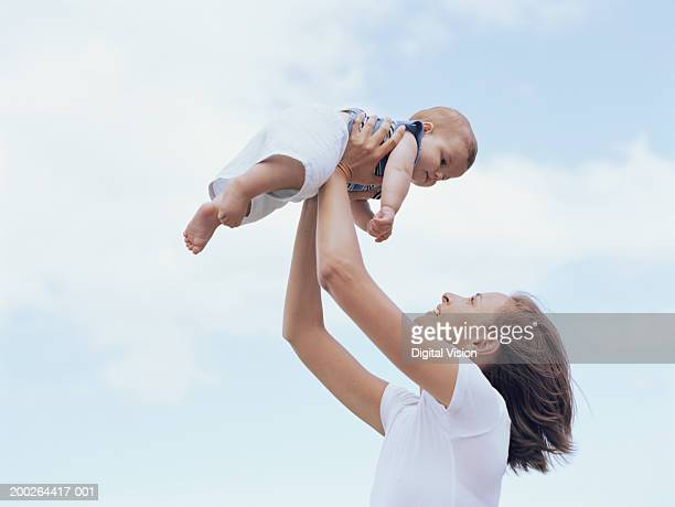 Mother holding up baby boy (6-9 months), outdoors, side view