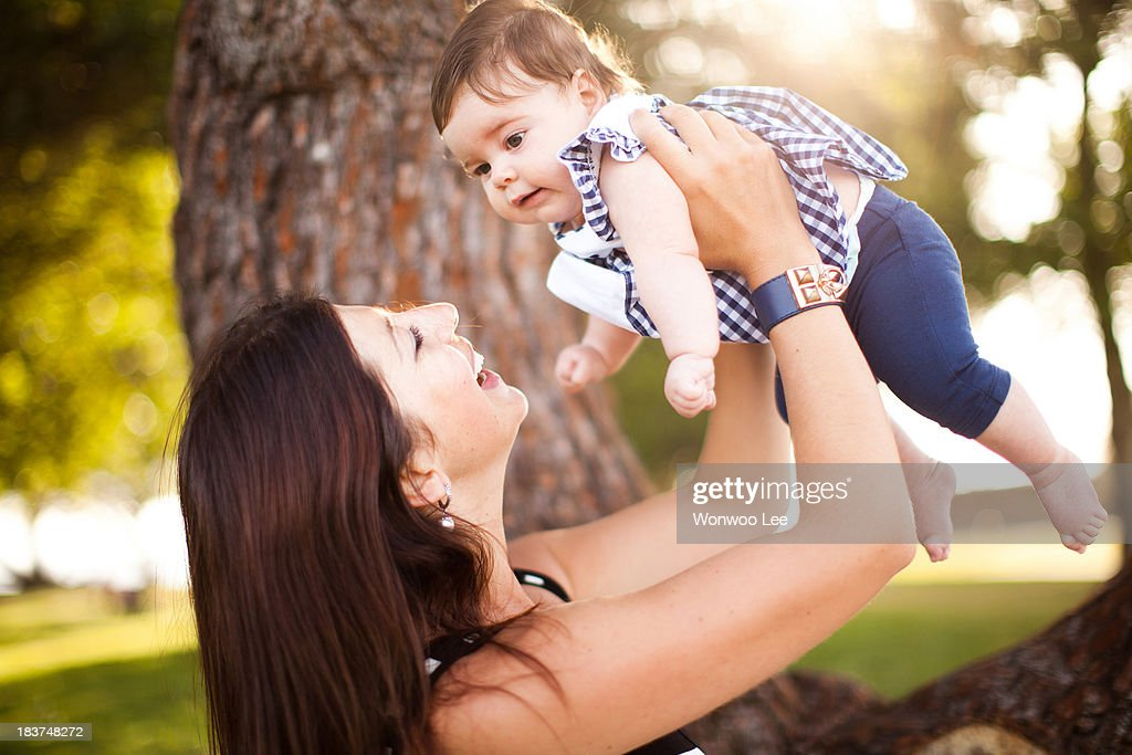 Mother holding up baby daughter : Stock Photo