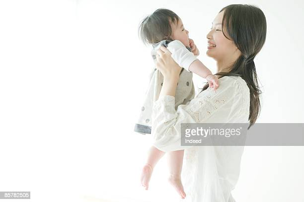 Mother holding up baby girl, side view