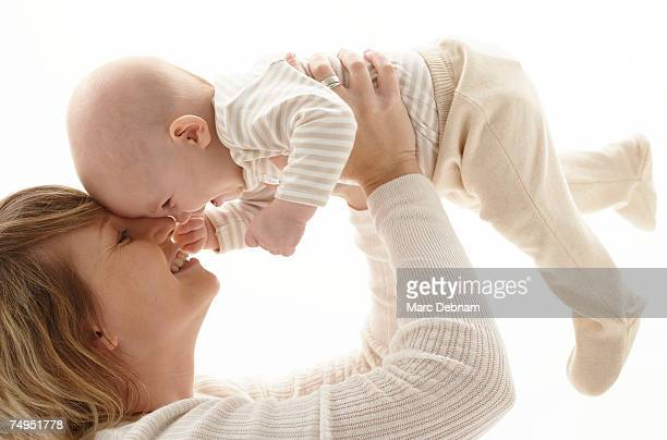Mother holding up baby girl (3-6 months) smiling