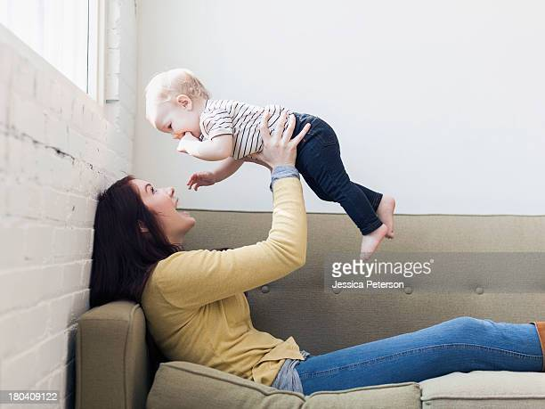 Mother holding up her daughter (12-17 months)