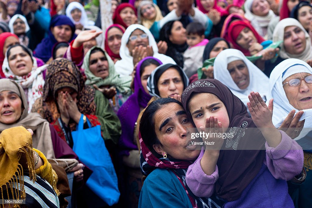 A mother holds a girl as they look towards a cleric displaying the holy relic believed to be the hair from the beard of the Prophet Mohammed at Hazratbal shrine on the Friday following Eid-e-Milad , or the birth anniversary of Prophet Mohammad on February 01, 2013 in Srinagar, the summer capital of Indian administered Kashmir, India. Thousands of Muslims from all over Kashmir visit the Hazratbal shrine in Srinagar to pay obeisance on the Friday following Eid-e-Milad , or the birth anniversary of Prophet Mohammed. The shrine is highly revered by Kashmiri Muslims as it is believed to house a holy relic of the Prophet Mohammed. The relic is displayed to the devotees on important Islamic days such as the Eid- Milad when Muslims worldwide celebrate.