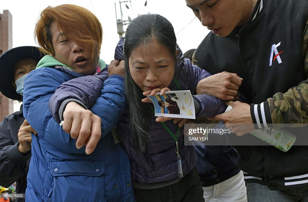 A mother holds a picture of her son after a male student body was recovered from the Wei-Kuan complex which collapsed in the 6.4 magnitude earthquake, in the southern Taiwanese city of Tainan on February 10, 2016. The developer of a Taiwan apartment complex that collapsed during a strong earthquake was arrested February 9, as rescuers reported hearing signs of life in the rubble where some 100 people are still trapped. / AFP / SAM YEH