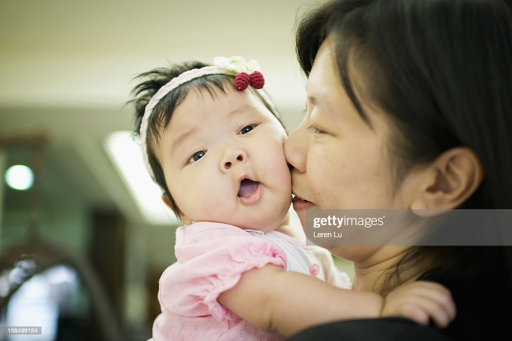 Mother holds baby in her arms : Stock Photo
