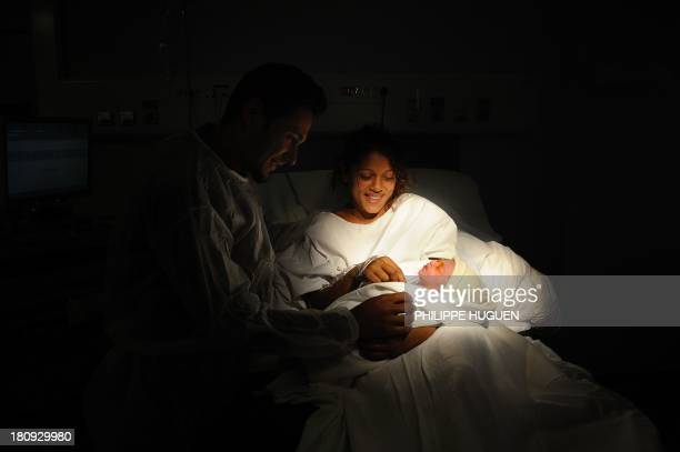 A mother holds her baby after its delivery on September 17 2013 at the Lens hospital northern France AFP PHOTO PHILIPPE HUGUEN