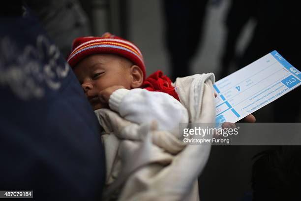 A mother holds her baby and a train ticket as they wait to board a train at Keleti station in central Budapest to take them to the Austrian border on...