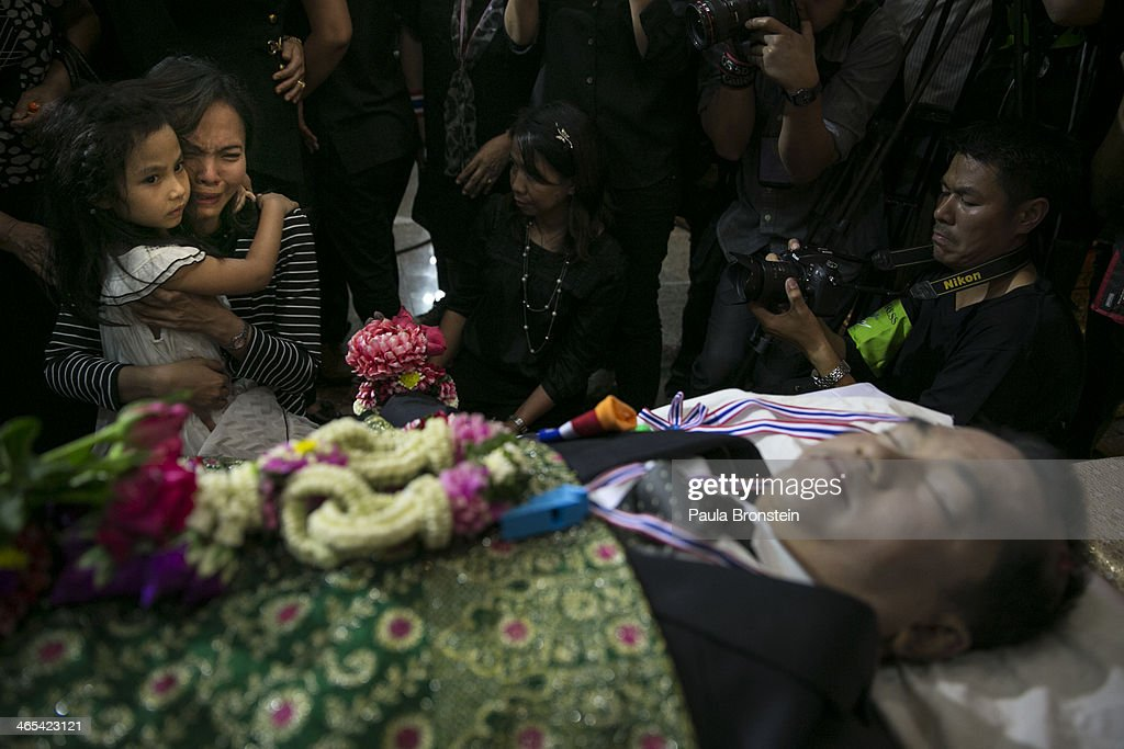 A mother holds her child grieving as hundreds of mourners pay their respects over the body of Sutin Tharatin, a core anti-government leader who was killed by gunmen yesterday, on January 27, 2014 in Bangkok, Thailand. Nine others were also injured during election related violence as protesters blocked polling stations as advanced voting took place in the capitol city. Bangkok Shutdown has been in effect for two weeks as the anti-government protesters continue to block major intersections. The Thai government imposed a 60-day state of emergency in Bangkok and the surrounding provinces in an attempt to cope with the on-going political turmoil but so far this decree has had no effect on the mass protests.