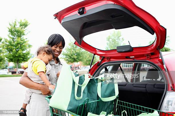 A mother holds her child on her hip while loading groceries