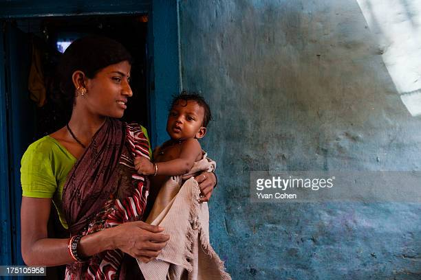 A mother holds her child outside her home in the Kolkata slum area of Fakir Bagan They are part of a program of care supported and run by the...