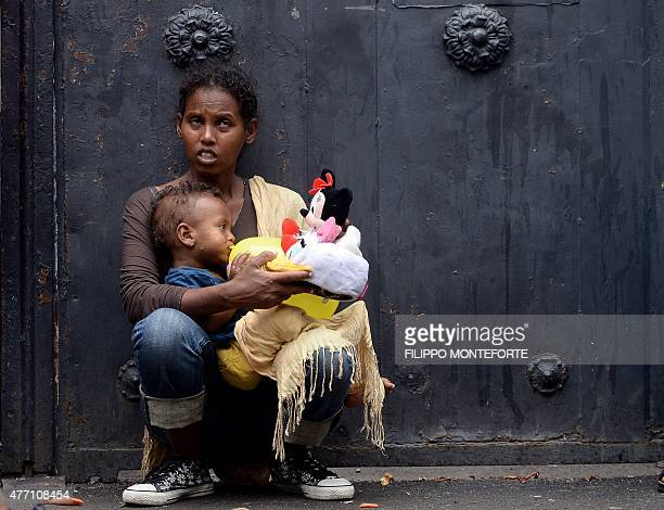 A mother holds her child with toys brought by aid workers outside 'Baobab' migration centre next to the Tiburtina train station in Rome on June 14...