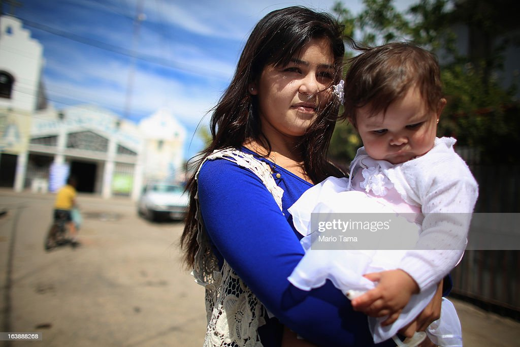 A mother holds her daughter after her baptism ceremony outside the Virgin of the Miracles of Caacupe church following Sunday Mass in the Villa 21-24 slum, where archbishop Jorge Mario Bergoglio, now Pope Francis, used to perform charity work, on March 17, 2013 in Buenos Aires, Argentina. Francis was the archbishop of Buenos Aires and is the first Pope to hail from South America. Some locals are now affectionately calling Francis, known for his charity work in the slums, the 'slum pope.'